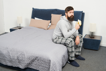 Calorie snack. Man bearded hipster sleepy face pajamas waking up bedroom interior. Healthy lifestyle. Rest and relax. Problem with early morning awakening. Get up early. Tips for waking up early. Stock Photo - 125009026