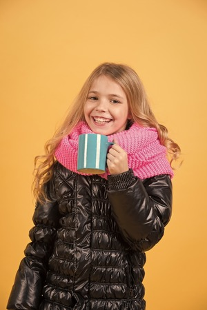 Autumn season relax concept. Child hold mug in black jacket and pink scarf. Hot drink in cold weather. Girl with blue cup smile on orange background. Tea or coffee break.