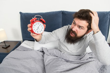 Get up with alarm clock. Overslept again. Tips for waking up early. Man bearded sleepy face bed with alarm clock in bed. What terrible noise. Turn off that ringing. Problem early morning awakening. Stock Photo - 125009069