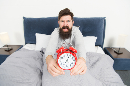 Problem early morning awakening. Get up with alarm clock. Overslept again. Tips for waking up early. Man bearded sleepy face bed with alarm clock in bed. What terrible noise. Turn off that ringing. Stock Photo