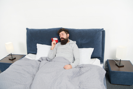 Tips for waking up early. Man bearded sleepy face bed with alarm clock in bed. What terrible noise. Turn off that ringing. Problem early morning awakening. Get up with alarm clock. Need more sleep. Stock Photo - 125009178