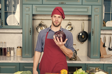 Confident at kitchen. Take old favorites and make healthful substitutions. Take favorite recipes and lighten them up. Man handsome chef holds violet cabbage thinking what healthy dish to cook.