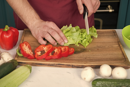 Be careful with knife. Chef teaches how quickly chop vegetables. Chop food safely and efficiently, ensure that you use the right tools. Learn how hold knife correctly and use right chopping technique. Stock Photo