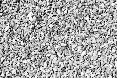 Small stones or gravels natural texture outdoors on sunny day on grey pebble background Stock Photo
