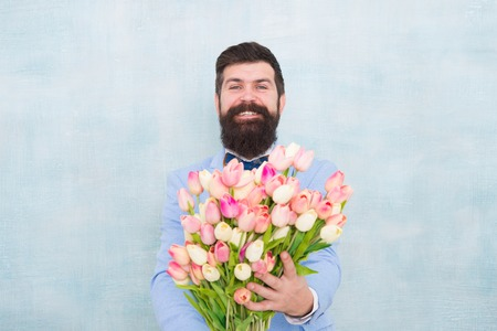 Gentleman romantic surprise for her. Flowers delivery. Gentleman romantic date. Birthday greetings. Best flowers for girlfriend. Spring holiday. Man bearded suit bow tie hold tulip flowers bouquet. Stock Photo