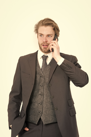 Conversation and new technology. Business fashion and success. Businessman or ceo in black jacket. Manager with beard on serious face. Man in formal outfit with mobile phone. Stockfoto