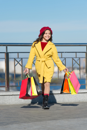 Autumn trend. little girl with purchase in shopping bags. Shopping day. happy little girl. Kid fashion look. Stylish child in french beret and fall coat. Thanks for your purchase. Nice purchase. Stock Photo