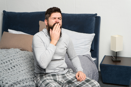 Sweet yawn. Get up early. Tips for waking up early. Man bearded hipster sleepy face waking up bedroom interior. Schedule for healthy lifestyle. Rest and relax. Problem with early morning awakening.