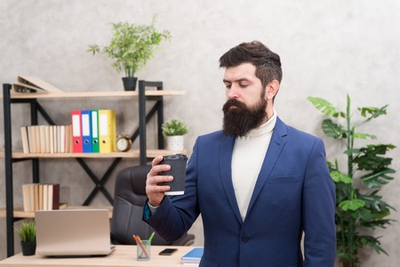 Reasons coffee improves office culture. Man bearded manager businessman entrepreneur hold cup of coffee. Relaxed manager drinking coffee. Boss enjoying energy drink. Worker start day with hot coffee.