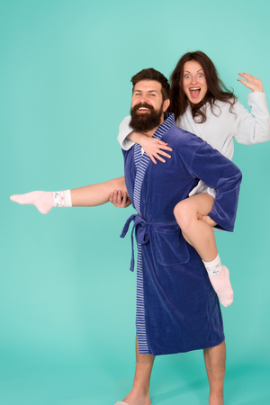 Happy family. Perfect morning. Having fun. woman and bearded man in robe. romantinc couple in love. man hipster love his woman. smiling woman hug man. man in robe hold woman in hands. Happy together. Stock Photo