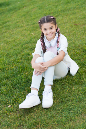 happy little girl. Audio book. Spring mood. Mp3 player. Kid in headphones. little girl listen music. Stylish child relax on green grass. audio e-book. Concept of audio book. listening audio book.