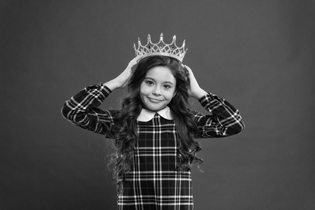 Monarch attribute. Kid wear golden crown symbol of princess. Every girl dreaming to become princess. Lady little princess. Girl wear crown red background. Monarch family concept. Princess manners.