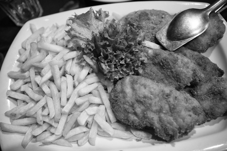 food. French fries and breaded meat or fish with green fresh salad leaves. dinner time. lunch in restaurant. business lunch. healthy food and dieting. hunger. eating in care.