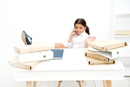 Having pleasure. Schoolgirl developing communication skills. Small school child having phone call. Little girl talking on mobile phone on lesson. Using communication technology in school education.
