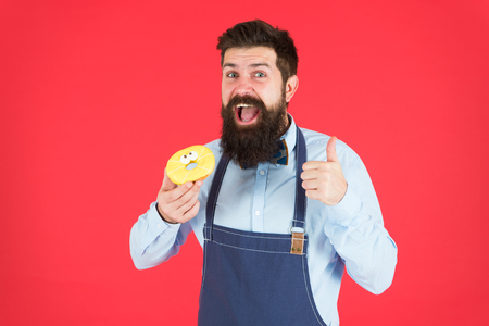 baker hold donut. Funny hipster. Sweet donut. Chef man in cafe. Diet and healthy food. Doughnut diet. Calorie. Feel hunger. Perfect donut. Bearded man in apron. Donut food. I love my job