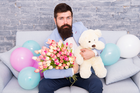 Romantic gift. Macho getting ready romantic date. Man wear blue tuxedo bow tie hold flowers bouquet. Best boyfriend ever. Romantic man with flowers and teddy bear sit on couch waiting girlfriend.
