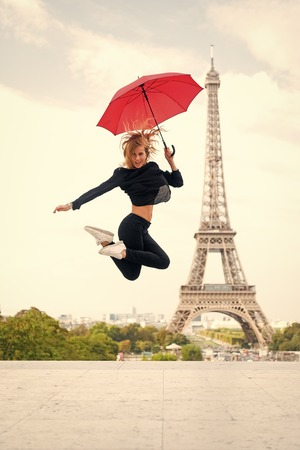 Girl with beauty look at eiffel tower. Woman jump with fashion umbrella. Parisian isolated on white background. Happy woman travel in paris, france. Travelling and wanderlust. Enjoy summer vacation.