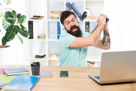Slow internet connection. Outdated software. Computer lag. Reasons for computer lagging. How fix slow lagging system. Hate office routine. Man bearded guy headphones office swing hammer on computer.