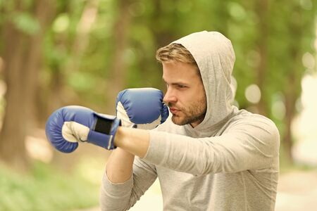 Attack or defend always be ready. Sportsman concentrated training boxing gloves. Athlete concentrated face sport gloves practice fighting skills nature background. Boxer handsome strict boxing.