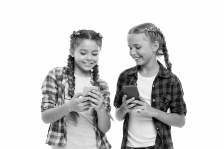 Girls cute small children smiling to phone screen. They like internet surfing social networks. Problem of young generation. Mobile phone and internet addiction or obsession. Mobile phone dependence. 写真素材