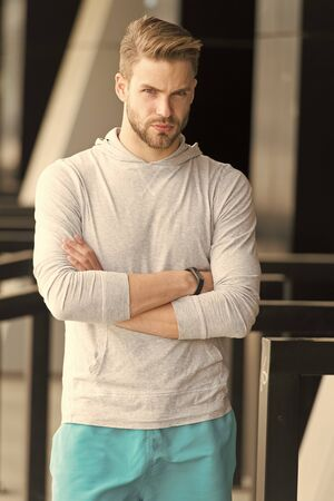 Sport is the way of his life. Guy bearded and attractive cares about appearance. Man with bristle on serious face ready to workout urban background. Man beard keep body good shape healthy lifestyle.