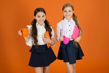Selecting tea for breakfast. Cute schoolgirls holding cups and books. Small girls enjoying school breakfast. Little children drinking morning tea or milk. School children having breakfast in morning. 写真素材 - 132015367