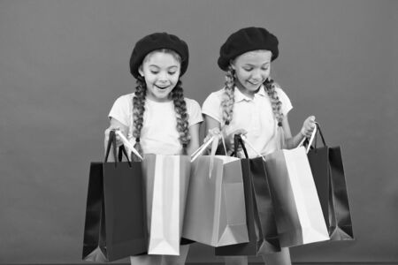 Children satisfied by shopping red background. Obsessed with shopping and clothing malls. Shopaholic concept. Shopping become fun with best friends. Kids cute schoolgirls hold bunch shopping bags. 写真素材