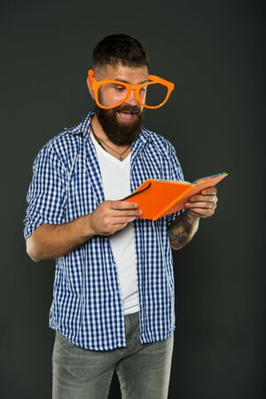Self education concept. Literary club. Reading book as hobby. Study is fun. Hipster bearded man funny eyeglasses hold notepad or book. Read this book. Comic and humor sense. Courses adult education.