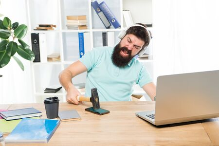 Spoiled communication. Failed mobile negotiations. Most annoying thing about work in call center. Incoming call. Annoying client calling. Man bearded guy headphones office swing hammer on smartphone.