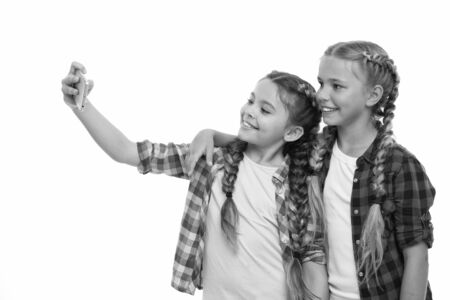 Girls cute small children smiling to phone screen. They like taking selfie for social networks. Problem of young generation. Mobile phone dependence. Mobile phone and internet addiction or obsession.