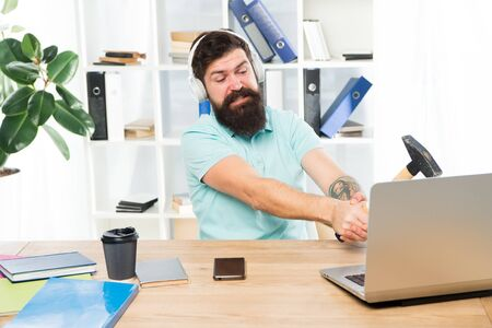 Computer lag. Reasons for computer lagging. How fix slow lagging system. Hate office routine. Man bearded guy headphones office swing hammer on computer. Slow internet connection. Outdated software.