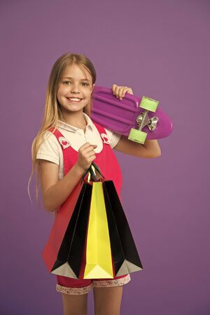 Little child smile with paper bags and skateboard on violet background. Happy girl with skate board and shopping bags. Shopping and black friday. Sport and active games. Happy shopaholic girl Stock Photo