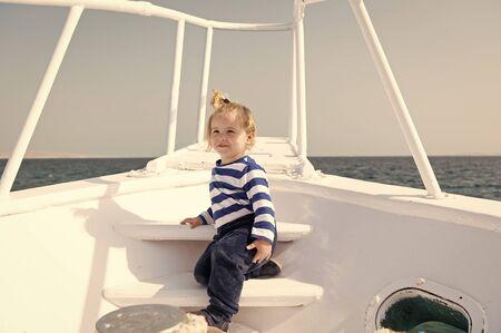 Kid concept. Little kid travel on ship. Kid enjoy sea travelling. Kid on board. Summer vacation and wanderlust. Standard-Bild - 132014253