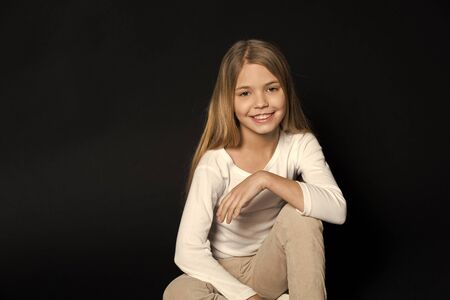 Happy child with fashion hairstyle on black background. Little girl smile with long blond hair. Beauty kid smiling with adorable look. Beauty salon. Keep calm and get your hair done.