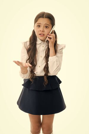 Fille mignonne cheveux longs parler smartphone fond blanc. L'expression du visage désespéré de l'enfant parle smartphone. La communication avec les parents est une partie importante du processus éducatif. Expliquez son erreur.