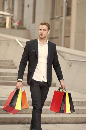 Luxury shopping. Boutique gallery client. Man shopper carries shopping bags urban background. Successful businessman choose only luxurious brands and shopping in high fashioned boutiques.