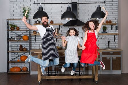 Family cuisine. Home interior. Culinary school. Happy family in kitchen. Mother and father with little girl. Little girl with parents in apron. Father, mother and child chef cooking. Family day