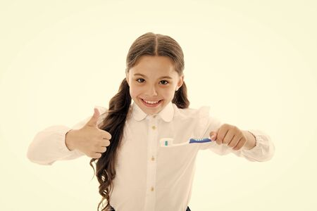 Girl brilliant perfect smile holds toothbrush with drop of paste white background. Child holds toothbrush and shows thumbs up. Child schoolgirl happy face cares mouth hygiene. Brilliant smile concept.
