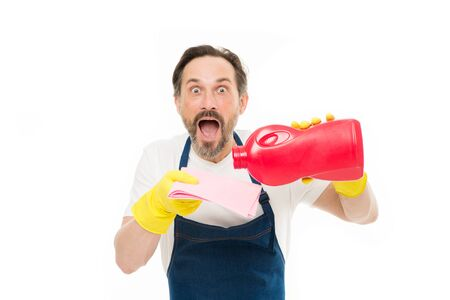 Keeping his home clean. Shocked cleanup man pouring home laundry detergent on wiper. Mature home keeper with open mouth wearing rubber gloves. Stock Photo