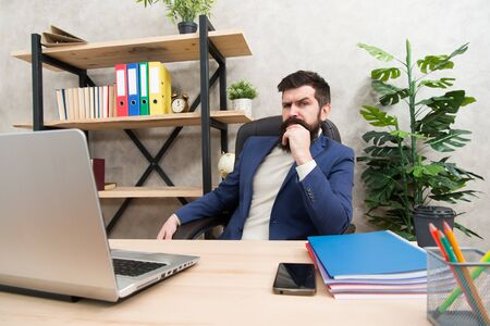 Developing business strategy. Risky business. Concentration and focus. Man bearded boss sit office with laptop. Manager solving business problems. Businessman in charge of business solutions. Imagens - 132014839