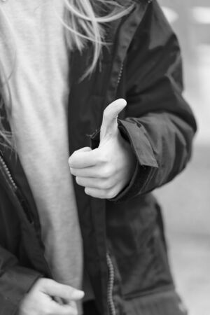 Hand of baby shows thumbs up gesture. Kid wear warm jacket show gesture of approvement or accept. She likes this. Thumb up gesture meaning like and agreement. Thumbs up and like concept.