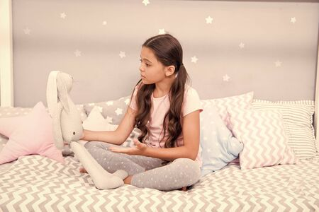 Child play grey rabbit. Best friends. Girl sit bed with grey bunny toy her bedroom. Kid prepare to go to bed. Wish sweet dreams to favorite toy. Girl kid relax and talk to bunny before fall asleep. Reklamní fotografie