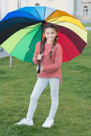 Multicolored umbrella for little happy girl. Positive mood in autumn rainy weather. Rainbow after rain. cheerful child. Spring style umbrella. Little girl hold colorful umbrella. Beauty with umbrella.