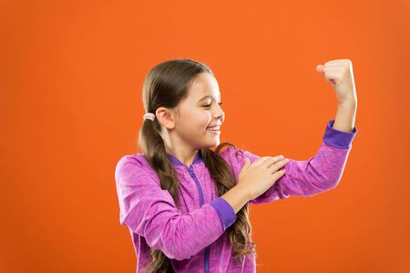 Strong and powerful. Raising strong kids. Satisfied with her strong healthy body. Feeling strong. Child cute girl show biceps power and strength. Girls rules concept. Upbringing advices for girls. Stock fotó
