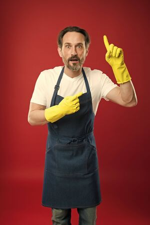 Just look over there. Mature man pointing finger up in yellow gloves.