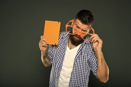 Hipster bearded man wear funny eyeglasses hold notepad or book. 스톡 콘텐츠