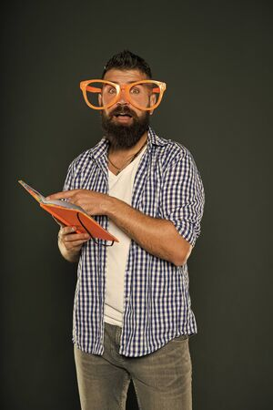 Bearded man in party glasses reading book. 스톡 콘텐츠