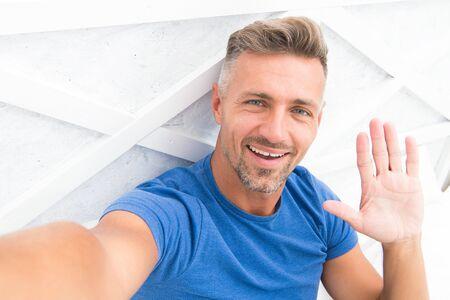 Hi there. Man taking selfie photo smartphone waving hand. Streaming online video. Mobile internet. Shooting for blog. Mature man blogger. Blog online content. Personal blog concept. Good morning. 版權商用圖片