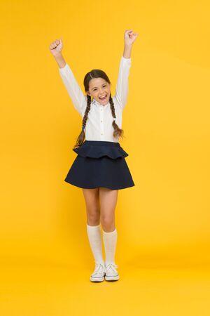 Powrót do szkoły. Małe dziecko studentka uwielbia szkołę. Emocjonalna uczennica. Świętuj dzień wiedzy. Wrześniowy czas na naukę. Dziewczyna urocza uczeń na żółtym tle. Mundurek szkolny i moda.
