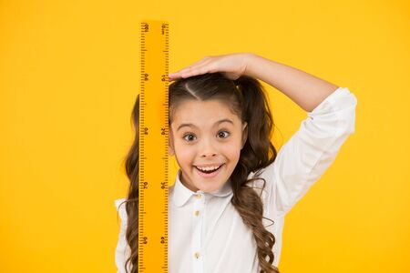 I am still growing. Tall kid. Kid school uniform hold ruler. Pupil cute girl with big ruler. Geometry school subject. Education and school concept. Sizing and measuring. School student study geometry